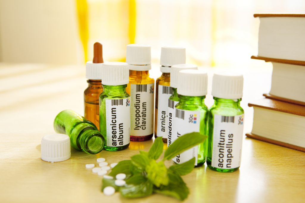 """Closeup of bottles with homeopathic remedies with Basil herb and Materia Medica and Repertory books on side, arnica montana, aconite napellus, lycopodium clavatum, arsenicum album aA